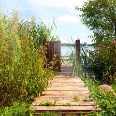 idyllische Landschaft mit Holzsteg und geöffneter Pforte am Schaalsee bei Zarrentin in Mecklenburg-Vorpommern