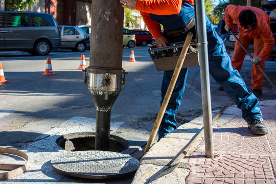 A Man Is Commanding A Machine For Cleaning The Manholes In The Street Before A Rain