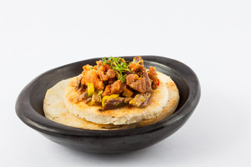 Colombian arepa topped with shredded beef and pork rind