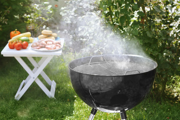 Barbecue grill with smoke on backyard