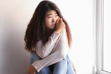 Sad young woman sitting near wall
