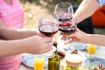 Happy family with glasses of wine having barbecue party outdoors