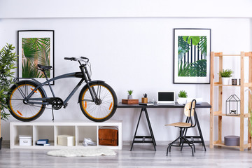 Modern room interior with bicycle and workplace