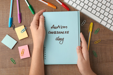"""Woman holding notebook with written words """"Autism awareness day"""" on table"""