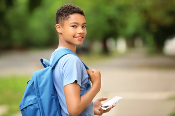 Charming African-American teenager with smartphone on city street