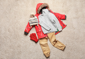 Wall Mural - Set of warm child's clothes on fabric