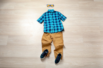Child's clothes and sneakers on wooden background