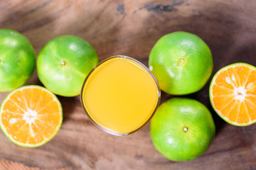 Top view of green tangerine orange fruit and juice on wooden background, healthy food
