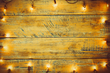Wall Mural - Christmas lights bulb on wood table. Merry christmas (xmas) background. topview, border design - rustic and vintage styles