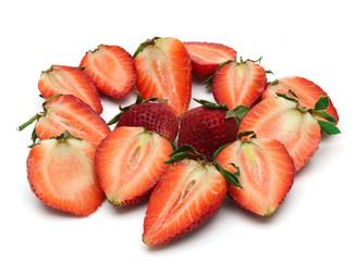 fresh sliced strawberries around two strawberries on white background