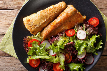 Healthy lunch: fried hake with tomato, radish and lettuce salad close-up. horizontal top view
