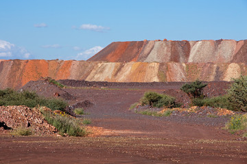 Mining dump with colorful layers of soil excavated from iron ore mining operations.