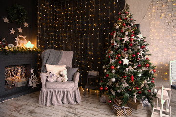 Interior of the room with a Christmas tree and a fireplace. Decorated for the New Year's holiday room with an armchair, teddy bears and garlands on the wall