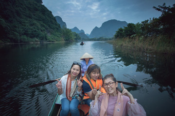 asian woman toothy smiling face happiness emotion sailing boat in ninh binh canal most popular traveling destination in vietnam