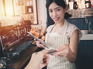 Young asian woman barista smiling standing behind the counter at coffee shop, Using tablet and customer payment by credit card, Cafe restaurant service concept,Owner small business concept.