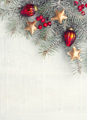 Fir branch with Christmas decorations on white  old wooden  background with copy space for text. Tone image