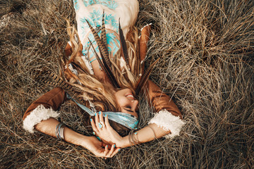 beautiful young boho girl in jacket lying down on grass