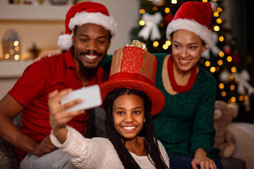 little girl with her parent taking selfie on Christmas.