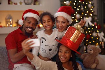 Christmas lovely afro American family making selfie.