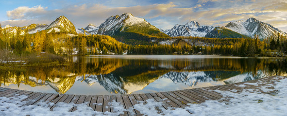 frosted bridge over the mountain lake Strbske Pleso in Slovakia, snowy mountains reflecting in the water