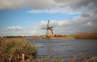 Historical windmill at the Kinderdijk area in the Netherlands with Blue sky and big white clouds