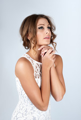 Beautiful young woman with makeup in a white dress praying. Portrait on a neutral grey background