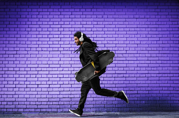 Handsome young dreadlocks skater with headphones running in a suit near the violet wall on the street.