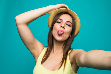 Young woman taking a selfie show tongue on a color background
