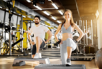 Attractive strong muscular trainer showing leg exercise with stepper to a lovely smiling girl with gloves in the gym.