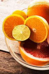 Citrus fruits - oranges, limes, grapefruits. On wooden background