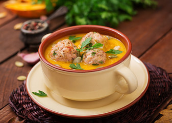 Delicious cream of pumpkin soup with meatballs made of turkey minced meat in a bowl on a wooden table. View from above. Thanksgiving Day.