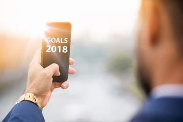 man holding phone with the words goals 2018