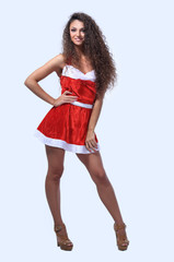 Young girl in short dressed as Santa Claus smiling.