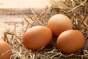 Fresh chicken eggs and straw on wooden background