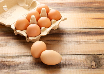 Fresh chicken eggs in egg box on wooden background