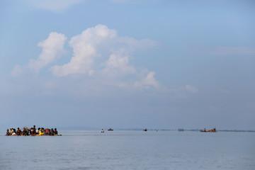 Makeshift rafts filled with Rohingya refugees sail towards the bank of Naf River after crossing the Bangladesh-Myanmar border, at Sabrang in Teknaf, near Cox's Bazar