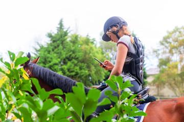 jeune fille sur son cheval avec son portable