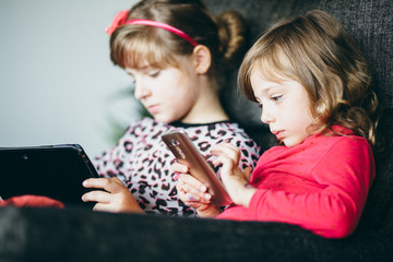 Little girls children kids using phone tablet computer playing games