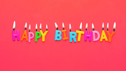 Happy birthday colorful candles on pink paper background