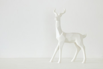 White reindeer on wooden table over white background