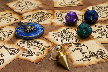 zodiac signs in old style with magic pendulum, blue horoscope ring and astrology dice
