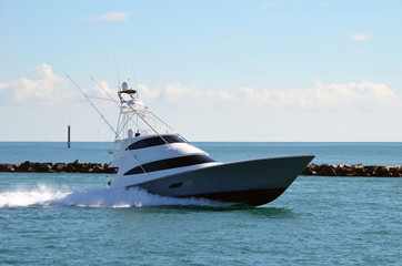 Upscale sport fishing boat speeding back to its home port after spending the day at sea.