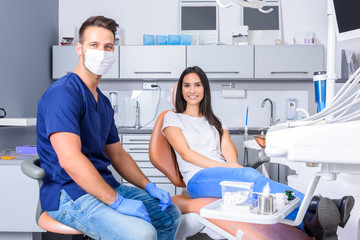 A young Dentist consulting a female Patient in the dental studio