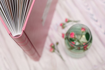 photobook with a hard cover on a wooden surface pages of the  photobook pink photo album with leatherette with a shield hands hold photo album