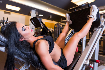 A young woman training her legs on a weight lifting machine