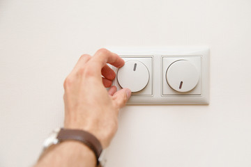 Saving energy concept: Human hand turning down electrical light dimmer switch or conditioner heat controller