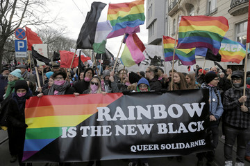 Participants hold rainbow flags as they take part in a rally, organised by Antifascist Coalition (Antifa) to mark 99th anniversary of Polish independence in Warsaw