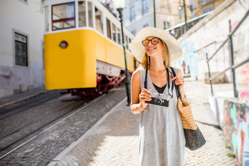 Portrait of a young woman tourist standing near the famous yellow tram traveling in the old town of Lisbon, Portugal