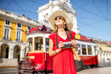 Portrait of a young woman traveler near the red old tourist tram on the Commerce square during the sunny weather in Lisbon city, Portugal