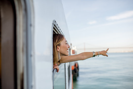 Young woman traveler pulling out face from the window in the water taxi in Lisbon, Portugal
